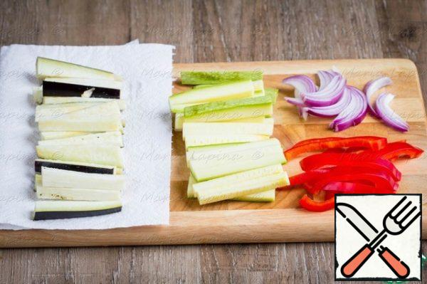 Prepare the vegetables for baking. Eggplant cut into cubes, put on a paper towel and add salt. Squash cut into slices, onions and peppers half rings or feathers.