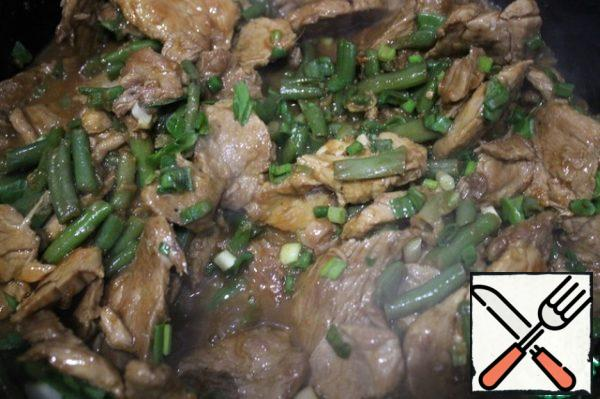The meat is almost boiled off the liquid. 2-3 tablespoons on the bottom are allowed. Spread to the meat beans and finely chopped green onions. Mix all and simmer for 3 minutes. Then add oyster sauce all quickly stir and simmer for another 30 seconds.