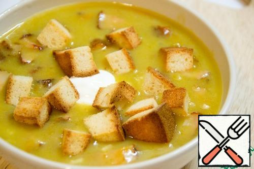 Soup serve with a spoon of sour cream and croutons.
