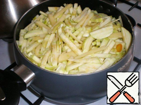 In the pot heated vegetable oil, fried crushed garlic and onion. Cut zucchini, potatoes, carrots and sent in a saucepan.