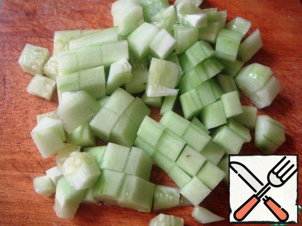 All vegetables wash, peel cucumbers from the skin (and remove large seeds, if any), cut into cubes.