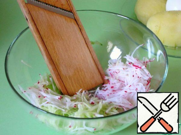 Peeled boiled potatoes, cucumbers, radishes, eggs to grate on a grater for carrots in Korean. Vegetables are obtained in the form of a long thin straw.