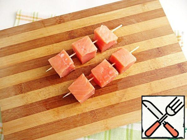 Salmon cut into cubes of 6 or 8 parts. String the cubes of salmon on wooden skewers.
