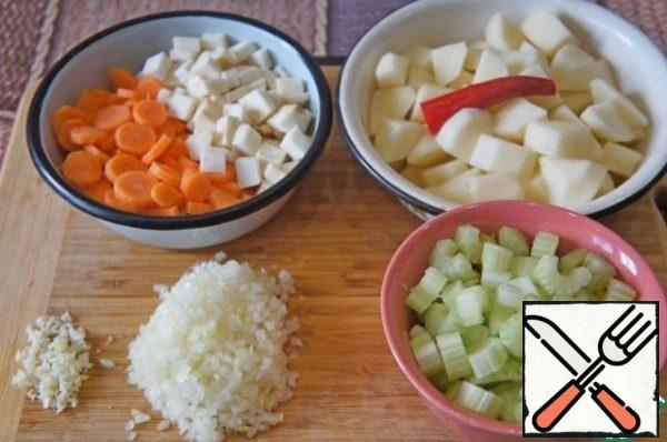 Rinse celery and chop the stalks into 0.5-1 cm. Carrots wash, peel and cut into slices of 0.5–1 cm. Peeled potatoes cut into cubes the size of 2 cm.  Remove the top and bottom of chili peppers. Chop the coriander. Cut into spinage.