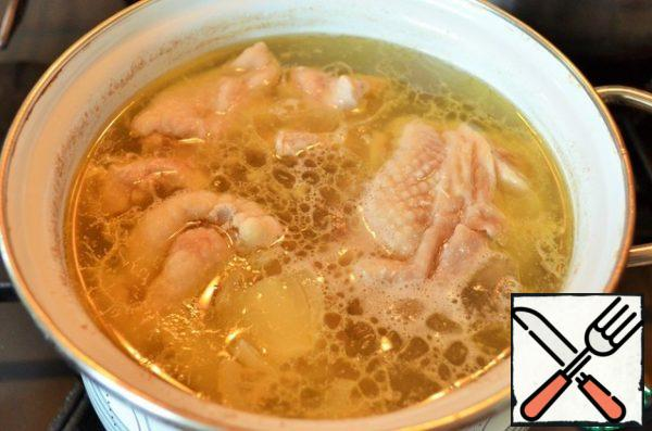 Prepare the broth. Chicken pieces with onions and carrots to boil into 1.5 l of water, 15 - 20 minutes. Use the bone from the breast.