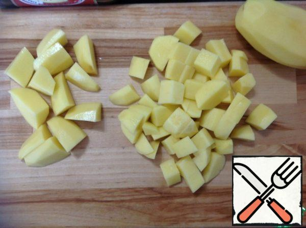 Peeled potatoes cut into on small and large slices.