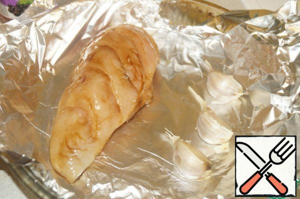 Lay out the fillets in an ovenproof form laid by foil. Next lay out the slices of garlic. Cover chicken and cloves of garlic with foil . Bake in a preheated 180 degree oven for about 20-25 minutes.