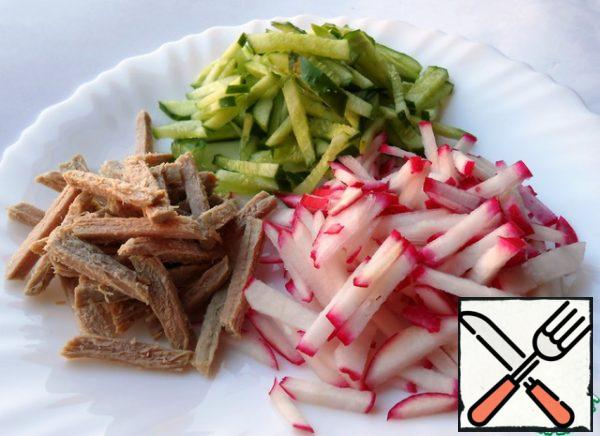 Cucumbers, radishes and boiled beef cut into straws.