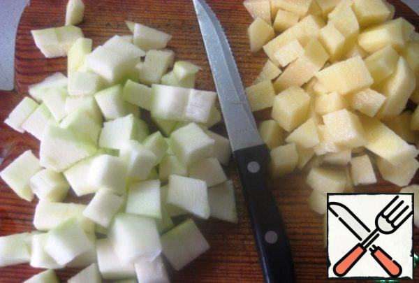 Put water on the fire, bring to a boil. Vegetables wash and to clear. Potatoes and zucchini cut into cubes (about the same size). As soon as the water boils, add potatoes.