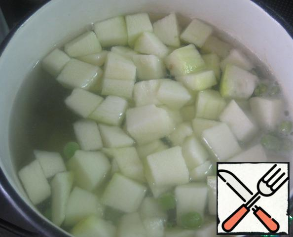 When potatoes boiled and boiled until half cooked, add to it zucchini and green peas. Cook everything together until the potatoes are ready.