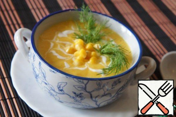 The finished soup spill on plates, add 1 tbsp of the corn, garnish with sour cream and herbs.