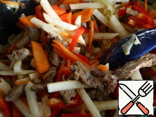 In the roasted meat add onions, continue to fry. Then add the carrots, radish. Fry and stir. Add bell peppers and continue to fry. Everything is fried on high heat, but should not burn.