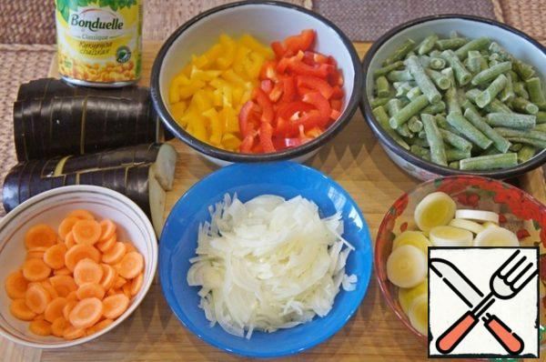 If beans is fresh should be boiled, drain in a colander and then cut into pieces. Chop the onion, leek cut into slices. Bulgarian pepper (I had half yellow and red) cut into strips carrots - sliced. Cut eggplant lengthwise into 4 pieces and then cut across into slices.