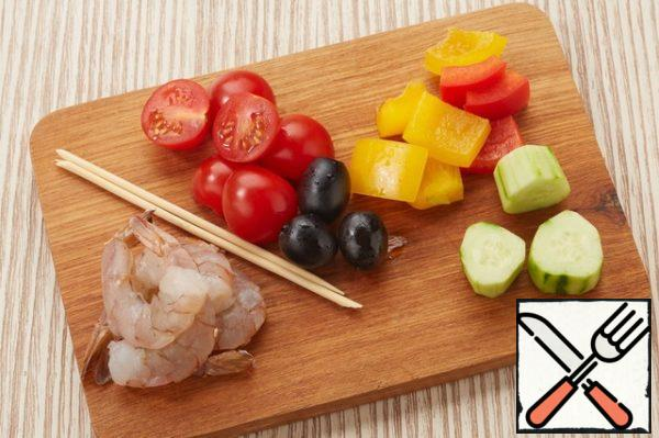 Soak skewers in cold water for 10-15 minutes. Clear the shrimp. Slice bell pepper into large pieces. On one skewer thread two shrimp in combination with pepper. The other, cucumber, cherry tomatoes, peppers. Skewer with shrimp,season salt, pepper and fry in a pan. In a martini glass pour gazpacho on top to put the skewers, insert straws and garnish with Basil leaf.