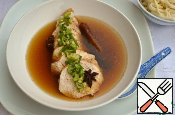 Chicken get out of the broth, cool slightly and cut into pieces of medium thickness. Pour in broth, in which it boiled, adding sesame-ginger dressing. Garnish with noodles.