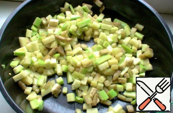 Clean the zucchini and eggplant, cut into cubes, in a frying pan pour oil, quickly fry vegetables on high heat for 2-3 minutes.