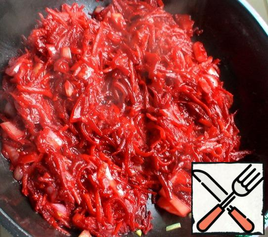 Peel and chop the onion. Also peel carrots and beets, grate on a coarse grater. Fry in a heated pan for 2-3 minutes, sprinkle with vinegar, add tomato paste and half a ladle of broth, simmer for 3 minutes. Sprinkle with chopped garlic. Remove from heat.