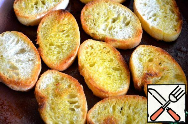 Baguette cut into slices of medium thickness and fry them in olive oil.