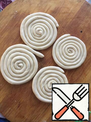 Take the sausage and pull it, roll it on the Board, and twist the dough into a spiral. Cover with a towel and leave for 10 minutes