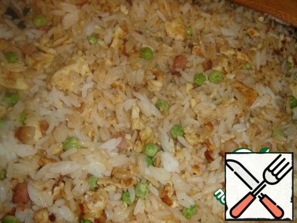 Add the boiled rice and mix in a pan. Fry all together for a few minutes until the rice is warm. At the end, add previously fried bacon, pour soy sauce, season with salt and pepper.