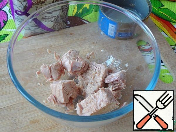 Drain the liquid from the tuna can and put the fish in a bowl.
