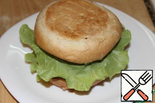 "Cover with a piece of cheese. Put on top of a hot cutlet. On the cutlet, put the leaf of salad with the back side up. And cover the ""bottom"" of the bread."