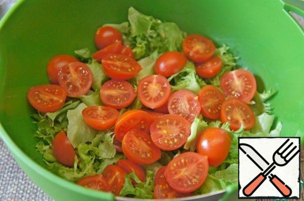 The tear lettuce with your hands and spread in a deep bowl. Cut cherry tomatoes in half or into quarters, add to the salad.