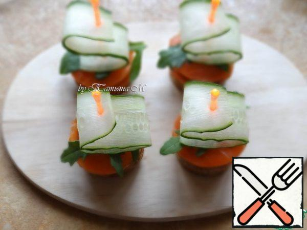 For salmon to put a piece of arugula, then with a skewer to pierce waves a slice of cucumber and set the skewer in the middle of canapés, stabbing it until the end;