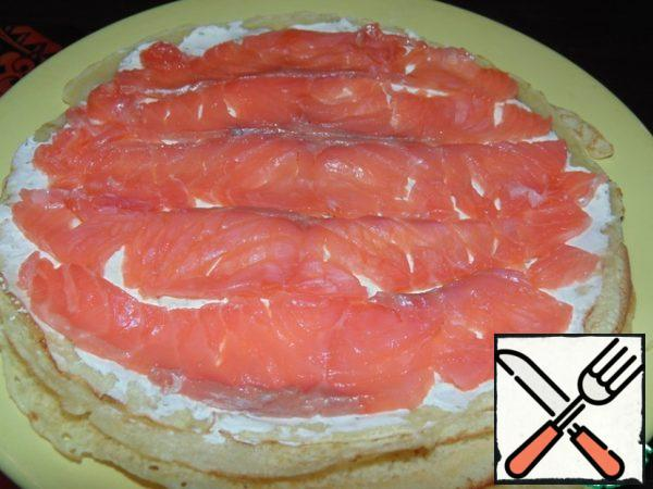 The fish is thinly cut and spread on the pancake and cheese.