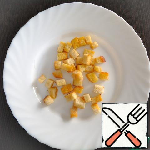 Cut the bread into cubes and fry in a pan in 2 tablespoons of olive oil.