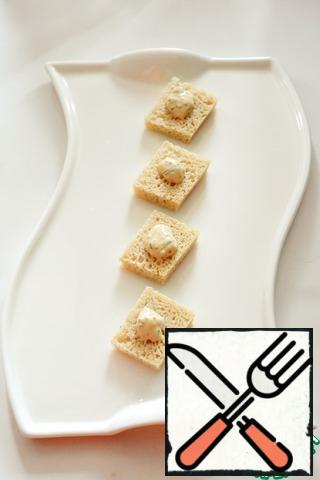 Cut the bread into small squares and dry them in a pan without oil. On each square of bread to drip a little sauce.