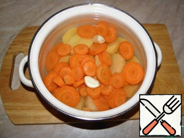 Potatoes to clear, cut, carrots cut into washers 1-1. 5 cm, garlic, peel the cloves, add to the pot, add water (water not too much), bring to a boil, add salt, a good seethe until tender.