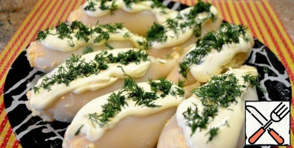 When serving, decorate the squid with mayonnaise and lemon juice and sprinkle with herbs.