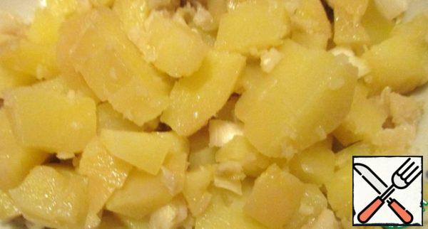 Boil potatoes in their skins, cool and cut into small cubes.