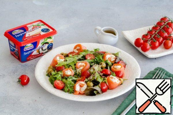 Mix with 1 tablespoon of dressing green salad mix, spread on plates. Next, put the rolls of fish and cheese, put tomatoes and olives on the leaves. Sprinkle with remaining dressing and serve.