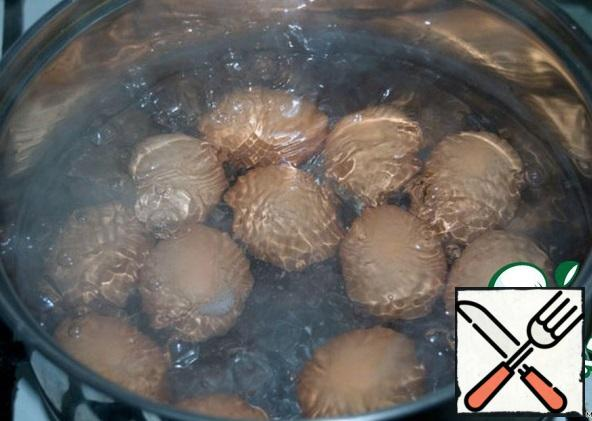 Boil eggs hard, pour over with cold water and peel.