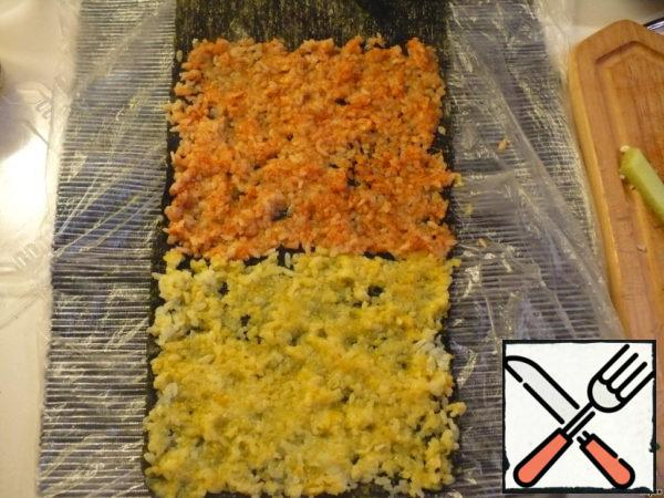 """And now - the most beautiful-mosaic. Divide the rice into 2 equal parts. Those who have flying fish caviar and black sesame can mix each of these parts with these components. I painted one part in turmeric, the second - in paprika. Take two sheets of nori, spread along the length of each other, the edges are glued together with water. On the first sheet spread yellow rice, then-red. I could not find my bamboo Mat, my daughter somewhere """"played"""", so I had to put a thick napkin in the package."""