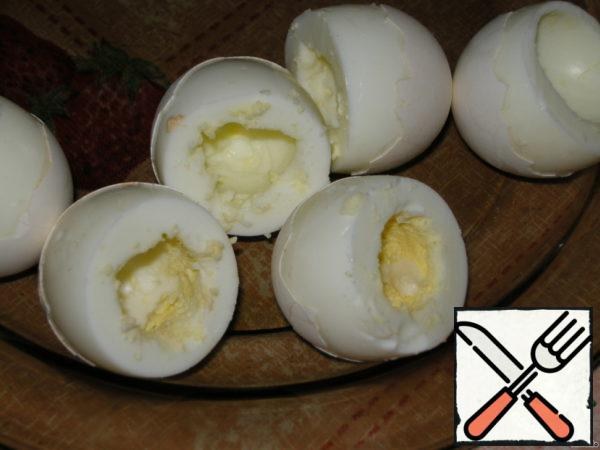 Boil and peel the eggs, as the photo to cut off the tops, yolks and egg white wipe to the filling on a fine grater.