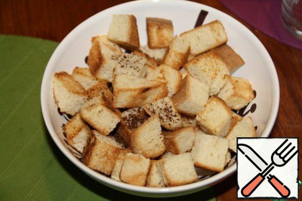 Prepare croutons: cut the bread into large cubes (about 2 cm by 2 cm), fry in a dry frying pan.