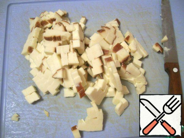 Then cut the sausage cheese into small cubes and add it to the minced meat.
