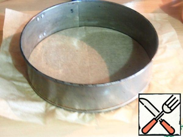 The bottom of the split mold for the cake lay baking paper. The dough is distributed in the form, making the bumpers, the bottom is often chopped with a fork and bake in a hot oven for 10 minutes at a temperature of 180 degrees. Remove the dough from the oven and cool slightly.