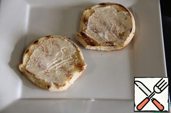 The lower piece of dried bread smeared with mayonnaise.