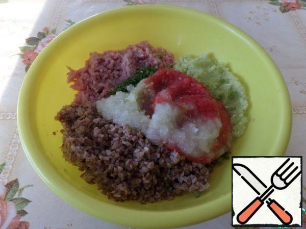 In a deep Cup put the boiled buckwheat, ground meat, shredded zucchini, carrots. Add 1/2 part tomato-onion mixture, herbs and salt ( to taste spices).