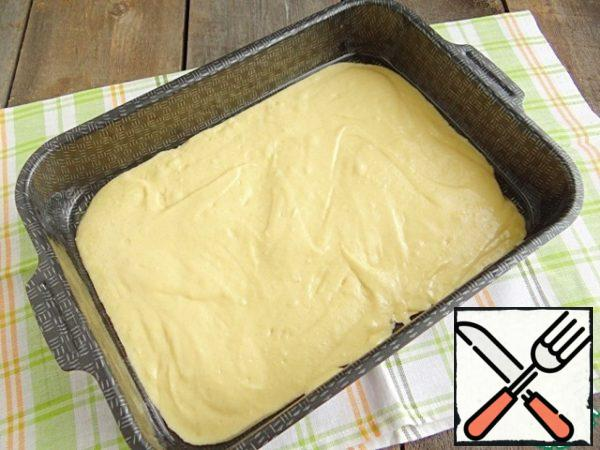 For baking this cake I use a rectangular shape size 23*30 cm Form smeared with vegetable oil. Pour half of the dough into the mold, using a spoon distribute the dough around the bottom.