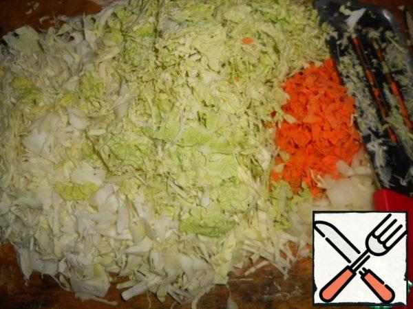 While preparing the dough, prepare the filling. Chop the cabbage, grate the carrots, peel and chop the onion.