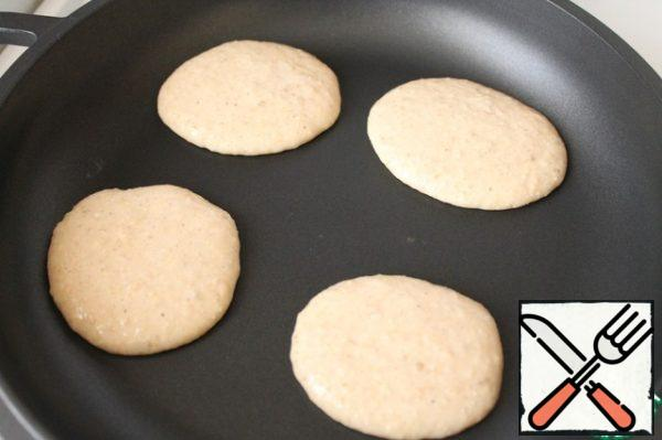 Heat the pan well. Bake the pancakes in a dry pan under the lid for about 1 minute on each side.