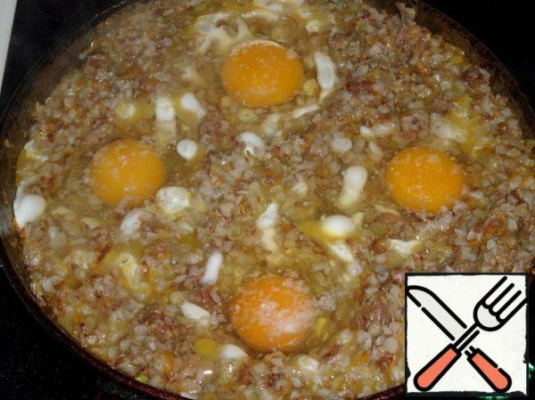 With a spoon make a small depression in the buckwheat porridge. In these recesses break the chicken egg. Salt. Cover the pan with a lid.