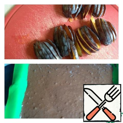Heat oven to 200 gr. Lay a baking sheet with a silicone Mat and put the dough, levelling it with a spoon. Bake the biscuit for 5-7 minutes. Meanwhile, wash and dry the plums, remove the bones. Cut the plum into thin slices.