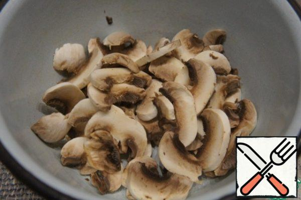 Remove the skin from the mushrooms and cut into thin plates (hats only).