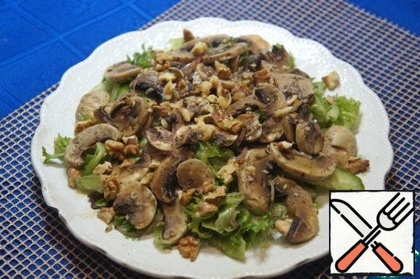 Put on a flat plate with a small slide. Put the pickled mushrooms on top, sprinkle all the nuts and pour the remaining dressing.